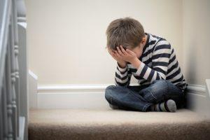 Junge sitzt auf Treppenabsatz und verbirgt sein Gesicht in den Händen.