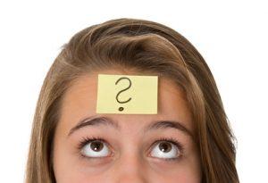 Mädchen mit Fragezeichen-Postit auf der Stirn